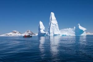Zodiac sailing past iceberg in Antarctica