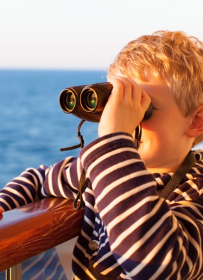 Boy with binoculars on cruise ship